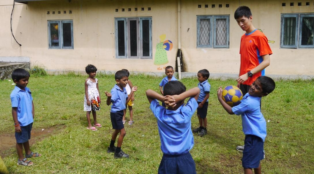 A volunteer coaching sports in schools in Sri Lanka plays a ball game with students